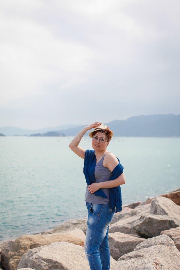 放松在海岸的有风夏日感到好 玻璃和牛仔裤的妇女在海岸走 库存图片