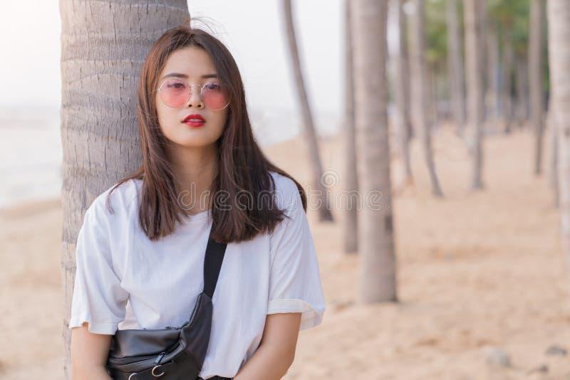 放松在海滩的亚裔美丽的女性年轻少年  免版税图库摄影