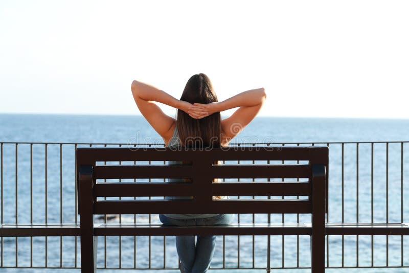 放松在海滩的妇女坐长凳 图库摄影