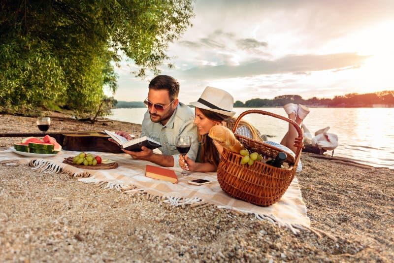放松在海滩的愉快的年轻夫妇,说谎在野餐毯子 免版税库存照片