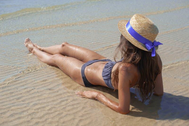 放松在海滩的时髦的愉快的年轻女人 和晒黑坐海滩的女孩在有波浪的海,晴朗的温暖的天气附近 ?? 免版税库存图片
