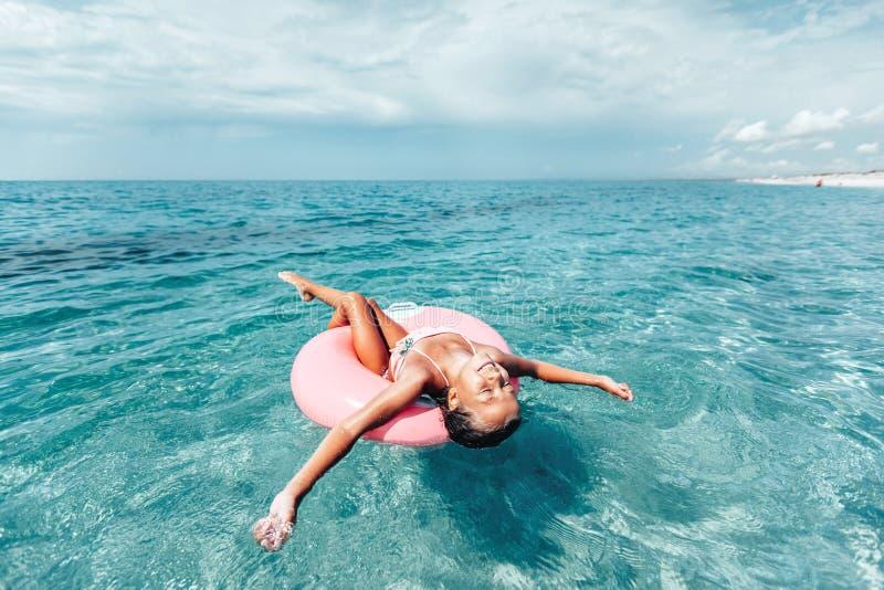 放松在海滩的lilo的孩子 库存照片