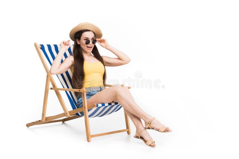 放松在海滩睡椅的美丽的激动的妇女, 免版税库存照片