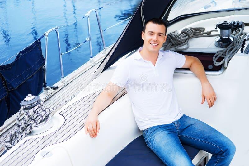 放松在海的一条小船的一个英俊的人 免版税库存图片
