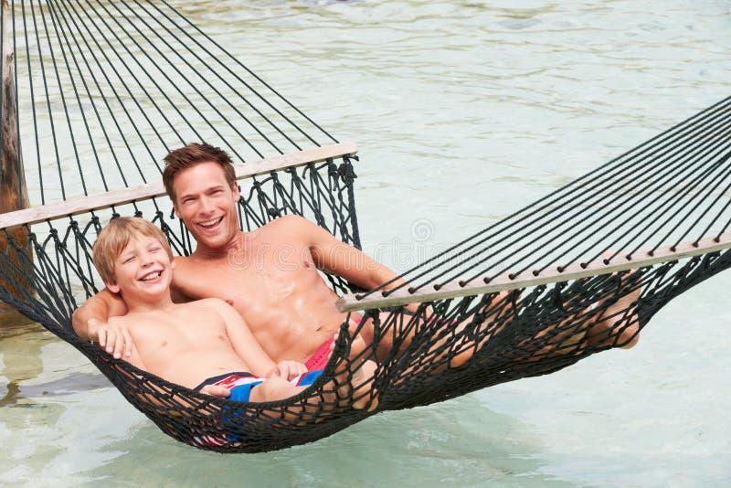 放松在海滩吊床的父亲和儿子 免版税库存照片