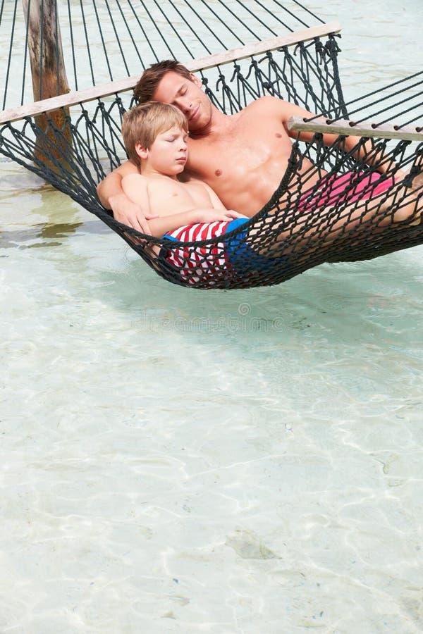 放松在海滩吊床的父亲和儿子 库存图片