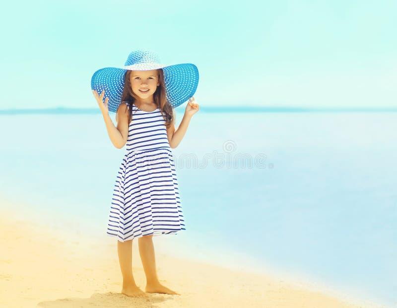 放松在海滩的一个镶边礼服和夏天草帽的美丽的小女孩在海附近 免版税库存图片