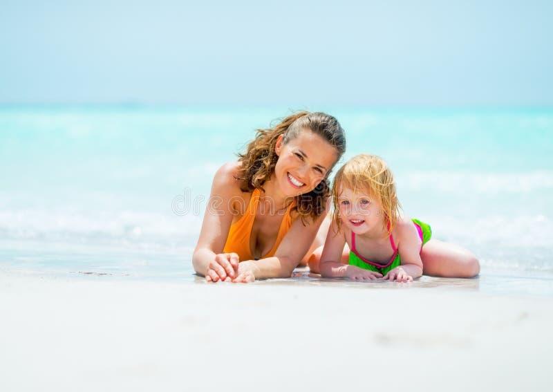 放松在海滩的母亲和女婴画象  免版税库存照片