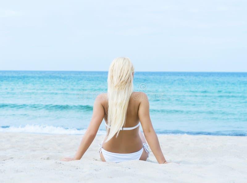 放松在海滩的泳装的美丽和运动的妇女 免版税库存照片