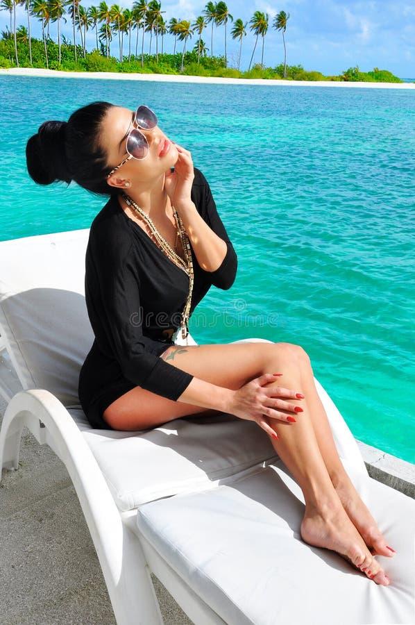 放松在海滩的肉欲的深色的夫人。 免版税图库摄影