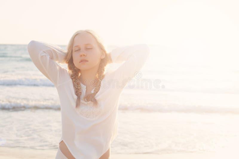 放松在海滩的年轻白肤金发的女孩在阳光下 库存照片