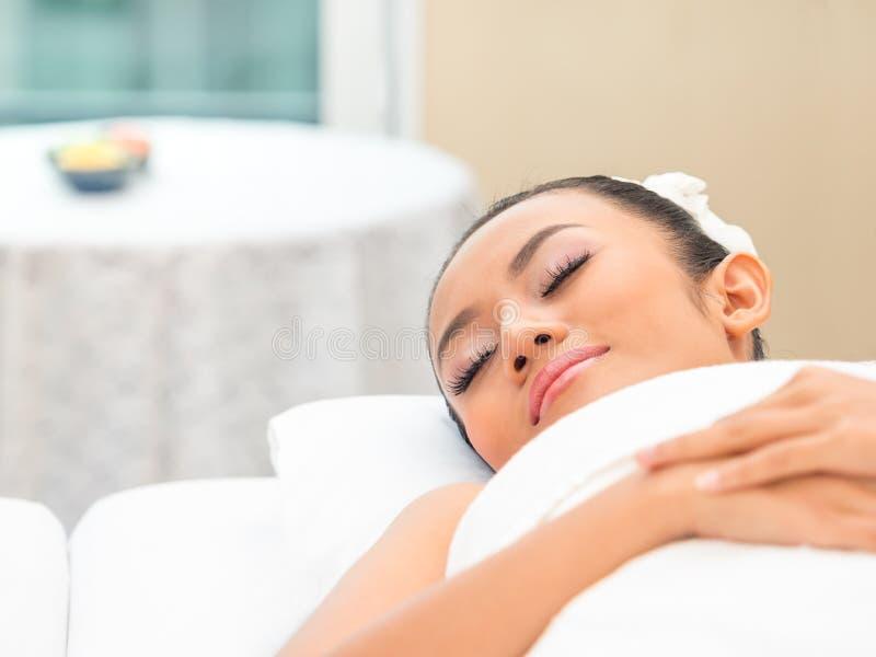 放松在温泉沙龙的年轻美丽的妇女 库存图片
