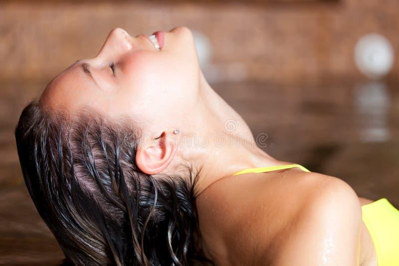 放松在温泉的美丽的妇女 免版税库存图片