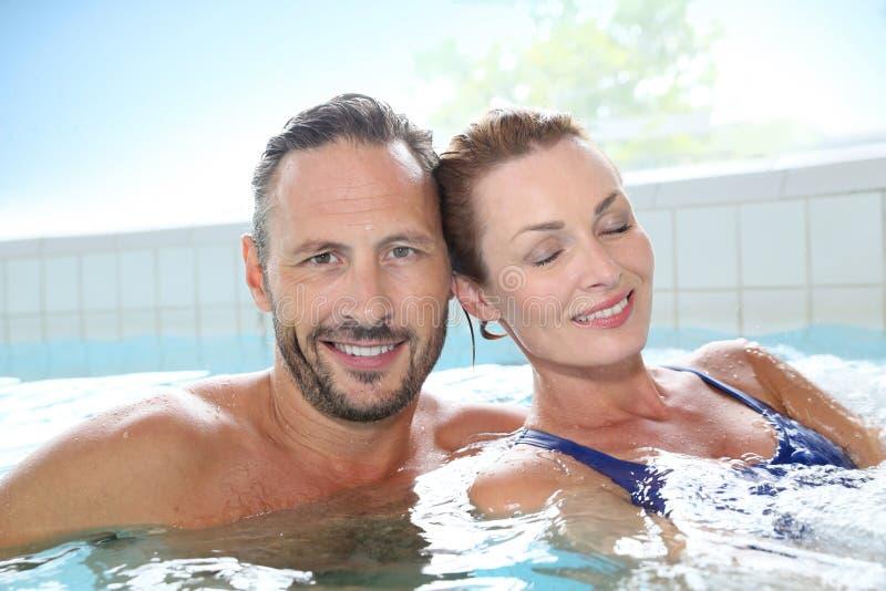 放松在温泉浴盆的愉快的夫妇 免版税图库摄影