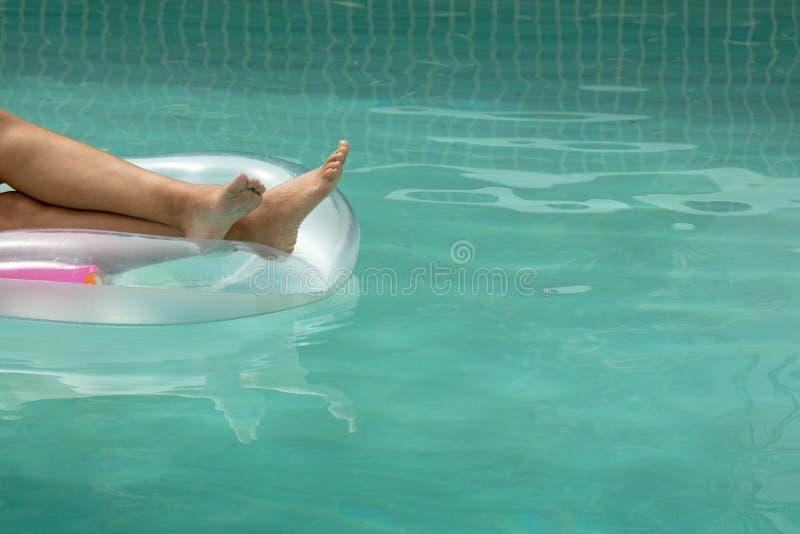 放松在游泳场的一支可膨胀的管的妇女在家后院  免版税库存图片