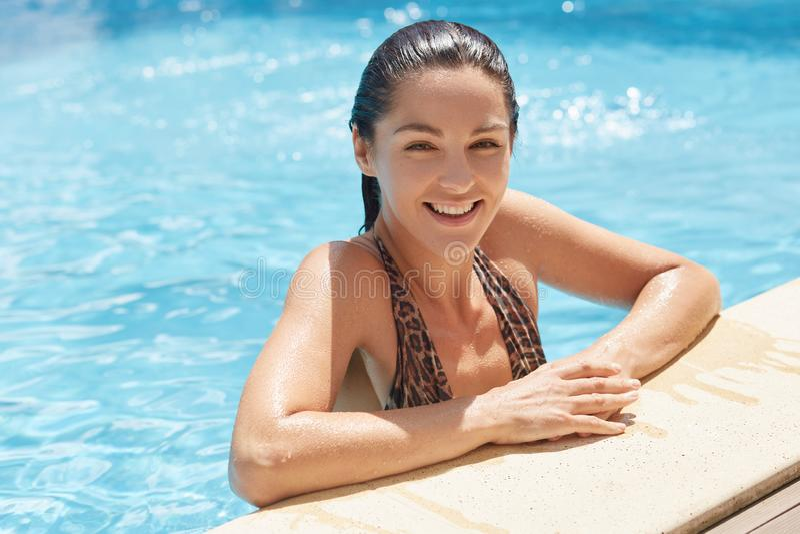 放松在游泳场的可爱的白种人女孩画象,摆在边缘附近 看照相机与的美丽的年轻女人 免版税库存照片