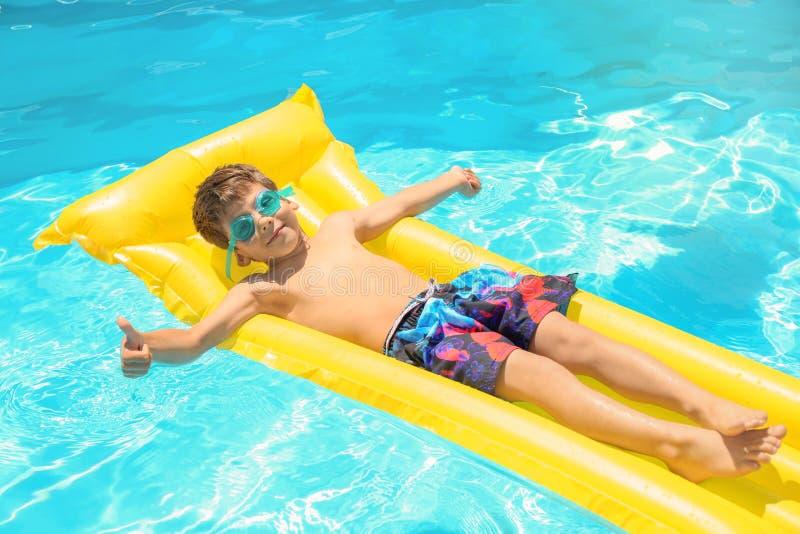 放松在游泳场的可膨胀的床垫的逗人喜爱的小男孩 免版税库存照片