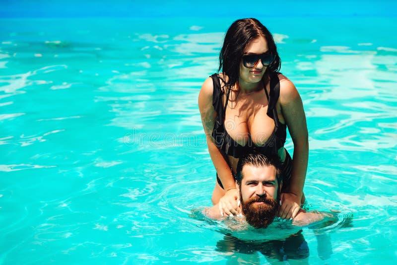 放松在游泳场的浪漫肉欲的夫妇 获得有胡子的人与热的女朋友的乐趣 ?? 愉快的恋人 免版税库存图片