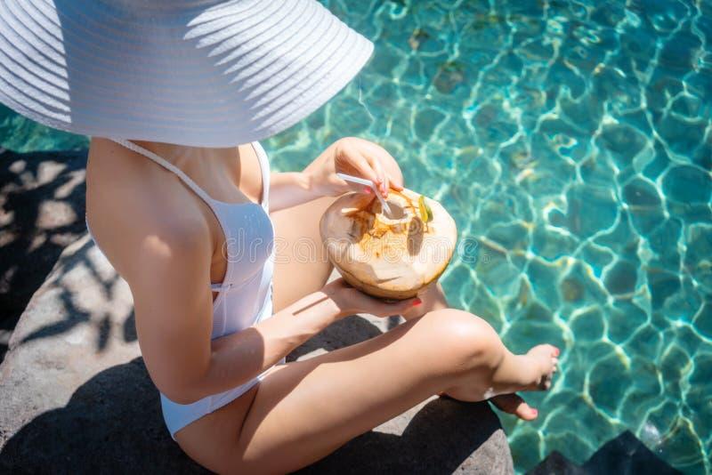 放松在游泳场的白色泳装的妇女 免版税图库摄影