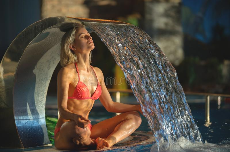 放松在游泳池温泉的美丽的运动的亭亭玉立的妇女画象  免版税图库摄影