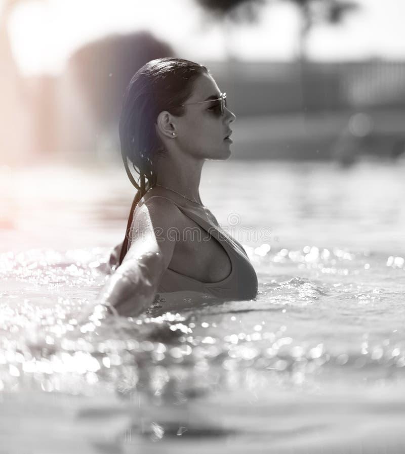 放松在游泳池温泉的蓝色游泳衣的美丽的被晒黑的妇女在昂贵的别墅附近在热的夏日 库存照片