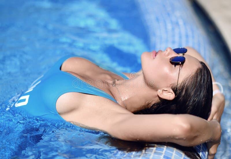 放松在游泳池温泉的蓝色游泳衣的美丽的被晒黑的妇女在昂贵的别墅附近在热的夏日 免版税图库摄影