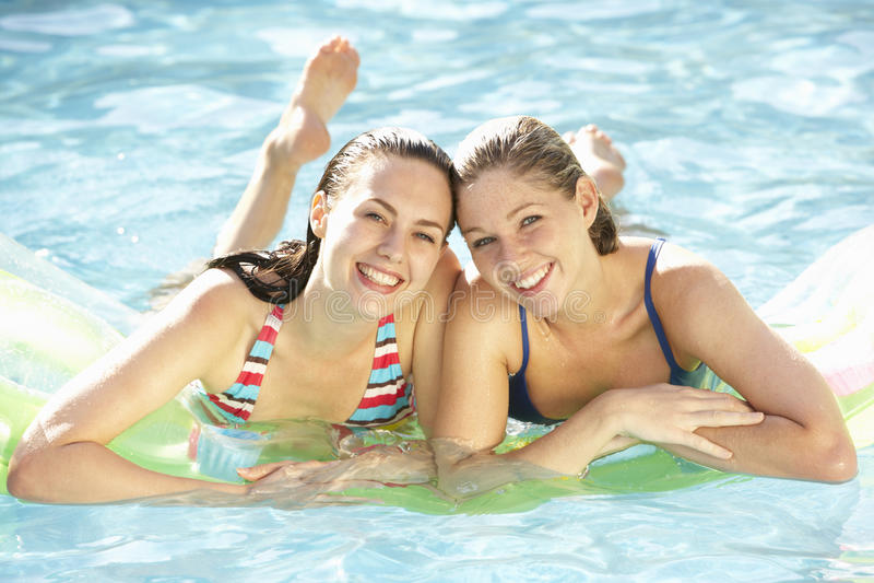 放松在游泳池的两个少妇画象  免版税库存图片