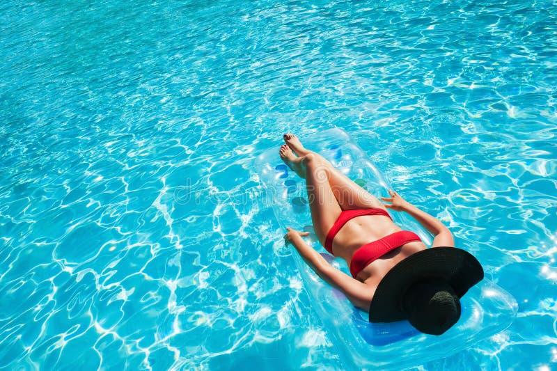 放松在游泳池的可膨胀的床垫的妇女 免版税图库摄影