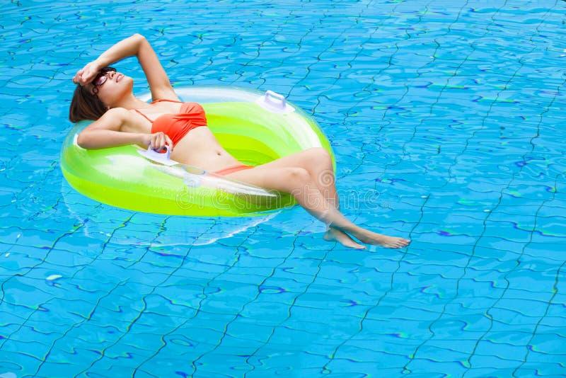 放松在游泳池的少妇 免版税库存照片