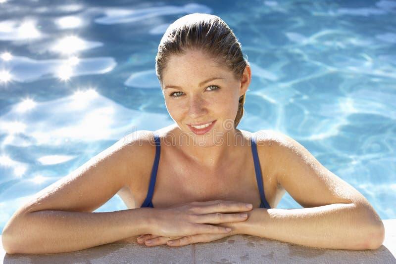 放松在游泳池的少妇 免版税库存图片