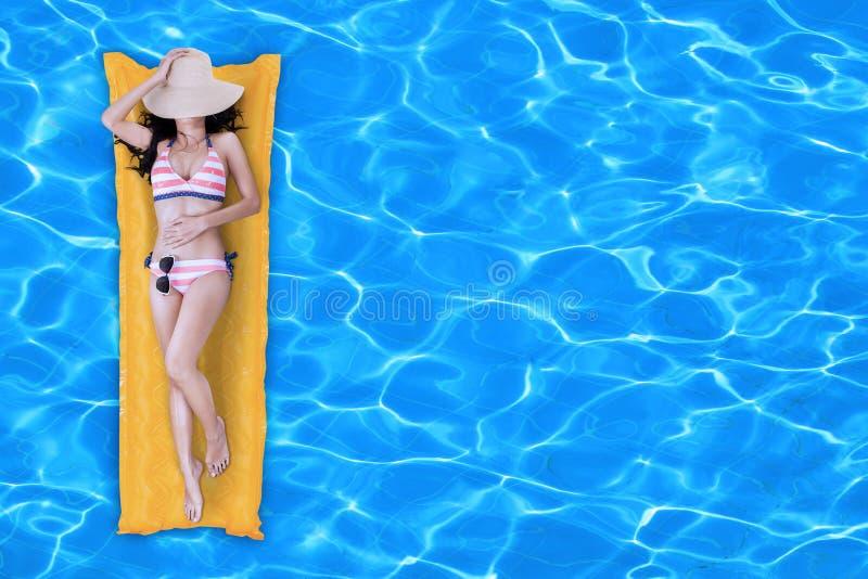 放松在游泳池的比基尼泳装的少妇 免版税库存图片