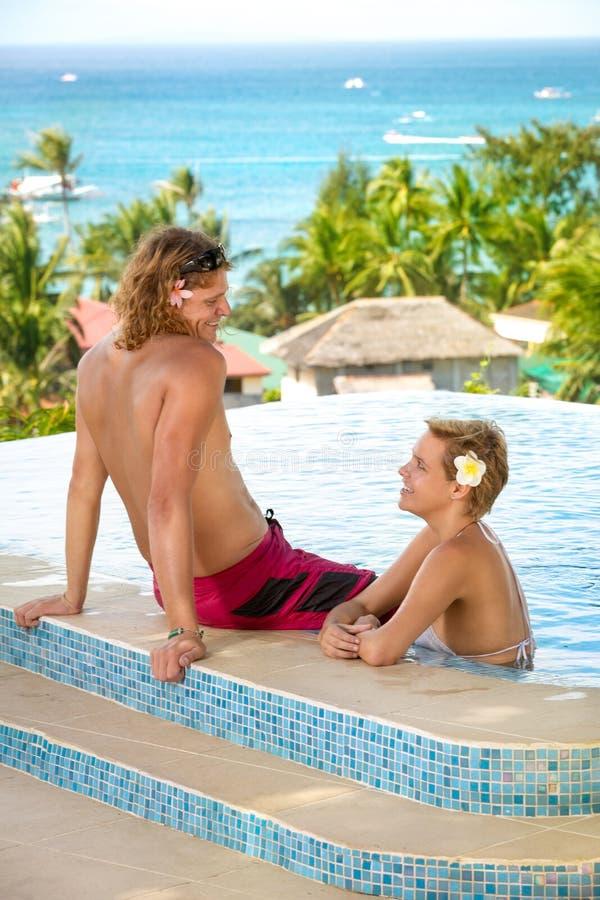 放松在游泳池的年轻夫妇 库存照片