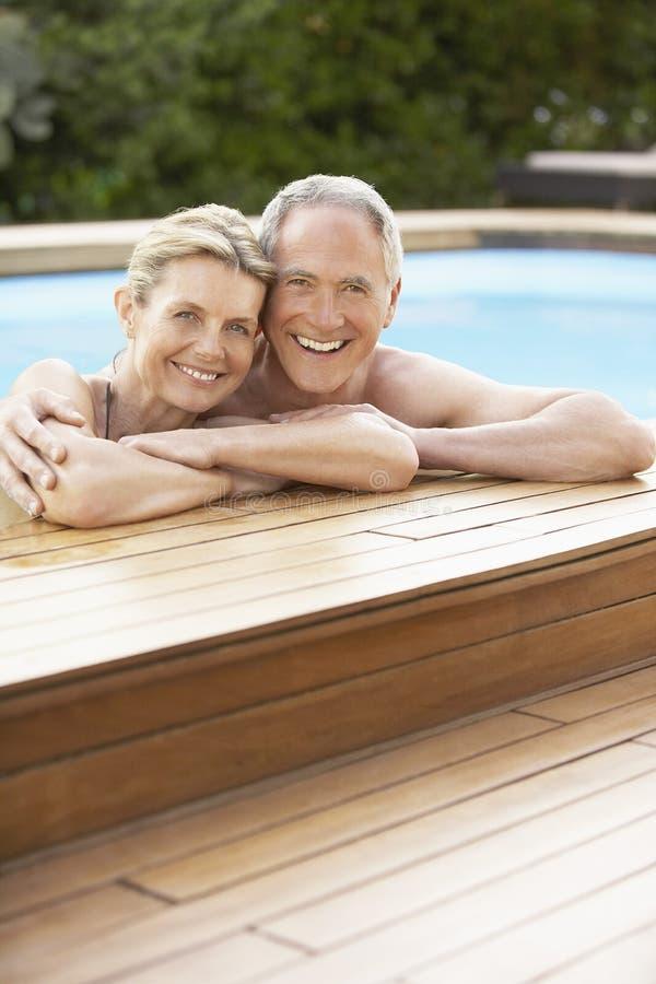 放松在游泳池边缘的夫妇 免版税图库摄影