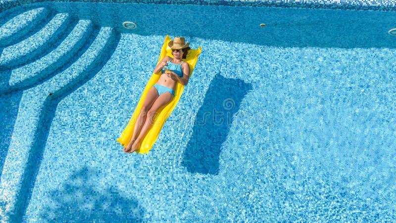 放松在游泳池,在可膨胀的床垫的游泳的美丽的女孩和获得乐趣在水中家庭度假,鸟瞰图 图库摄影