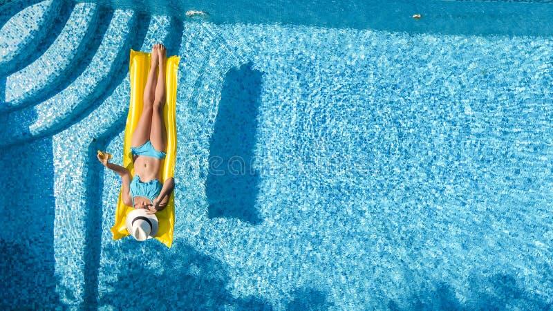 放松在游泳池,在可膨胀的床垫的游泳的美丽的女孩和获得乐趣在水中家庭度假 图库摄影