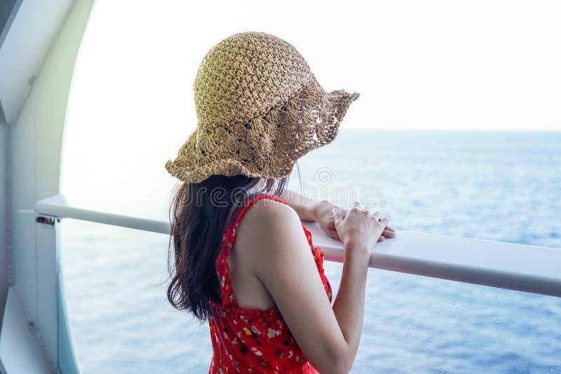 放松在游轮的妇女享受从阳台的海景 免版税库存照片