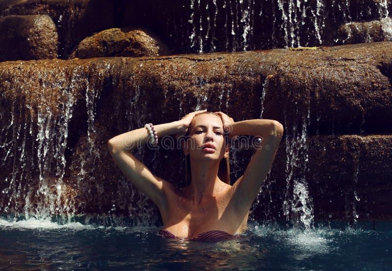 放松在瀑布下的比基尼泳装的性感的妇女在泰国 库存照片