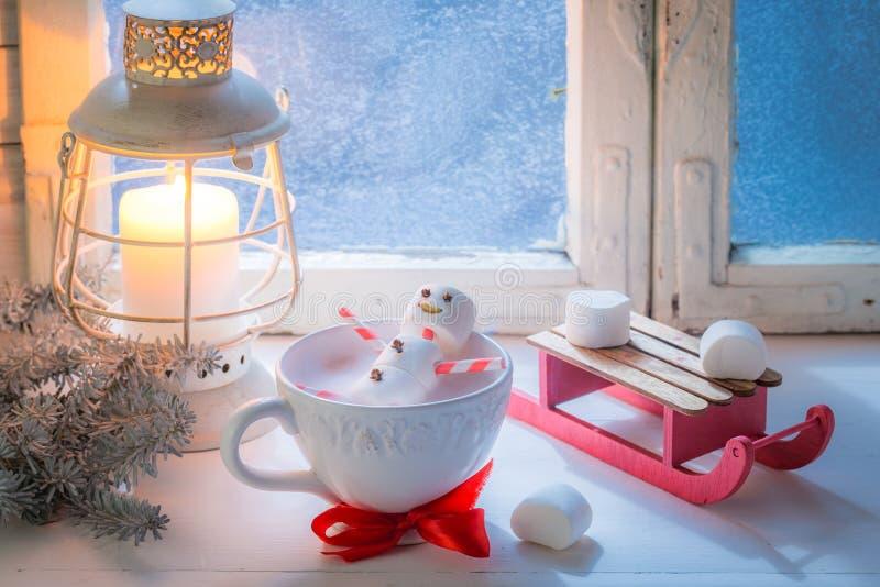 放松在热的可可粉雪人由圣诞节的蛋白软糖制成 免版税图库摄影