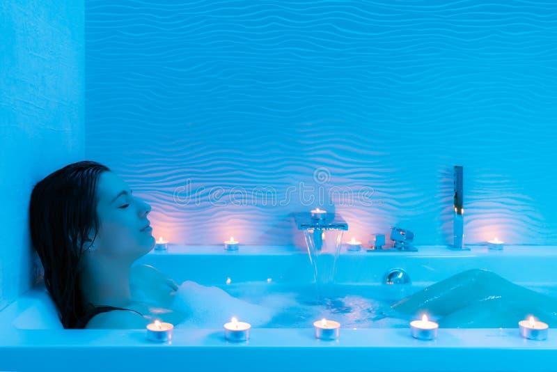 放松在热的泡沫浴的少妇 免版税库存图片