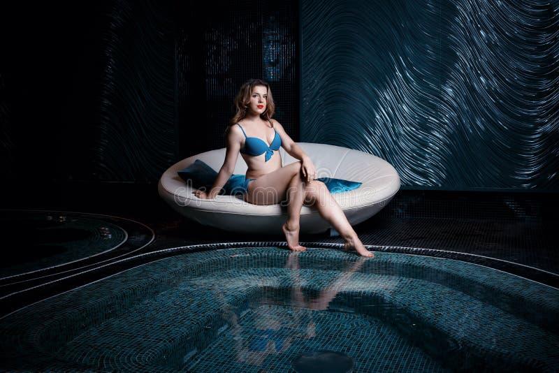放松在热的水池或极可意浴缸的比基尼泳装的美丽的年轻白肤金发的白种人妇女在温泉中心 免版税库存照片