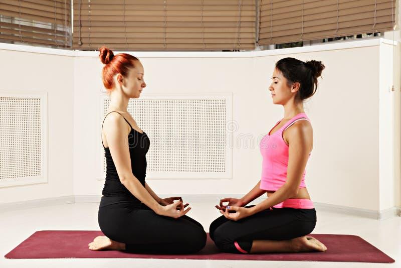 放松在瑜伽类的两momen 免版税库存照片