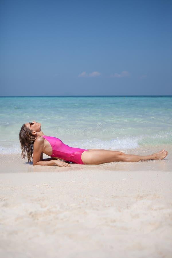 放松在白色沙滩的妇女在海附近 免版税库存图片