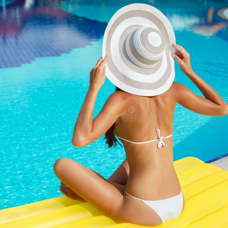 放松在白色游泳衣、帽子和太阳镜的游泳场的美丽的被晒黑的妇女画象  异乎寻常的模型 r 免版税库存图片