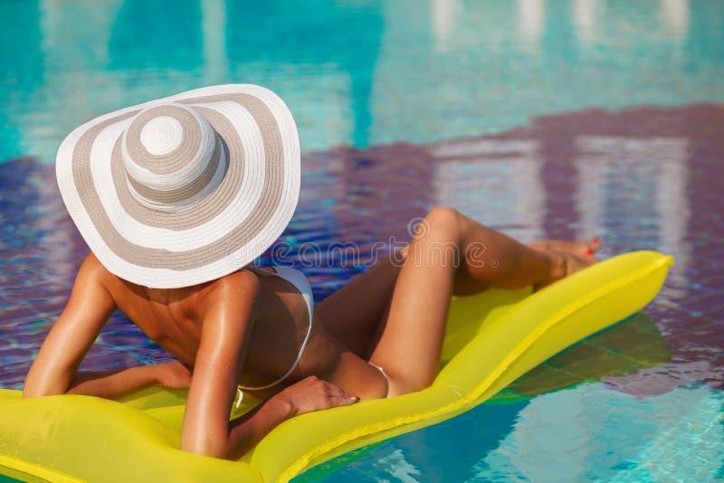 放松在白色游泳衣、帽子和太阳镜的游泳场的美丽的被晒黑的妇女画象  异乎寻常的模型 r 库存图片