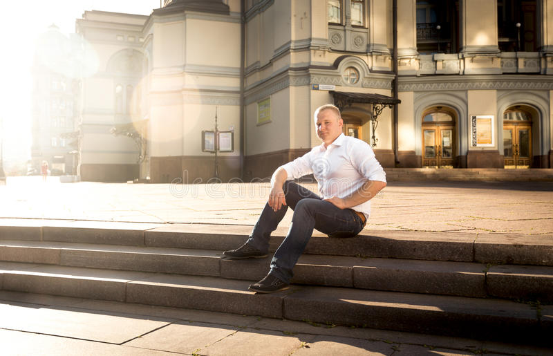放松在石台阶的时髦的人在大经典大厦 免版税库存图片