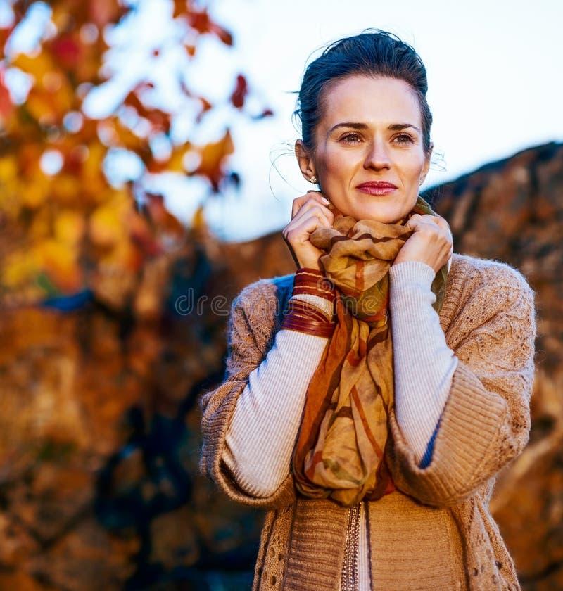 放松在秋天公园的微笑的棕色毛发的妇女 免版税库存照片