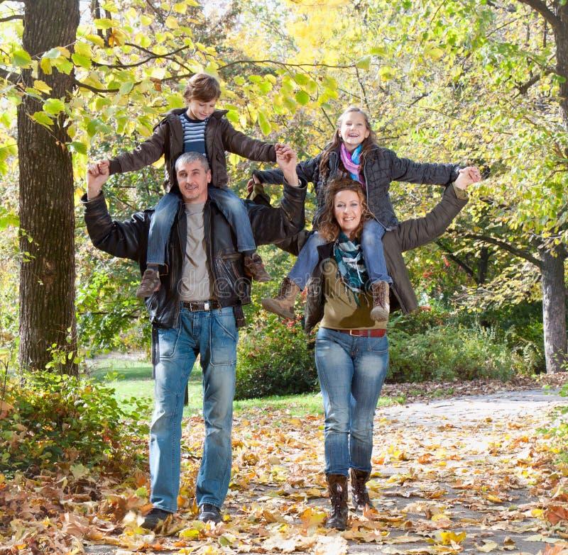 放松在秋天公园的愉快的家庭 免版税库存图片