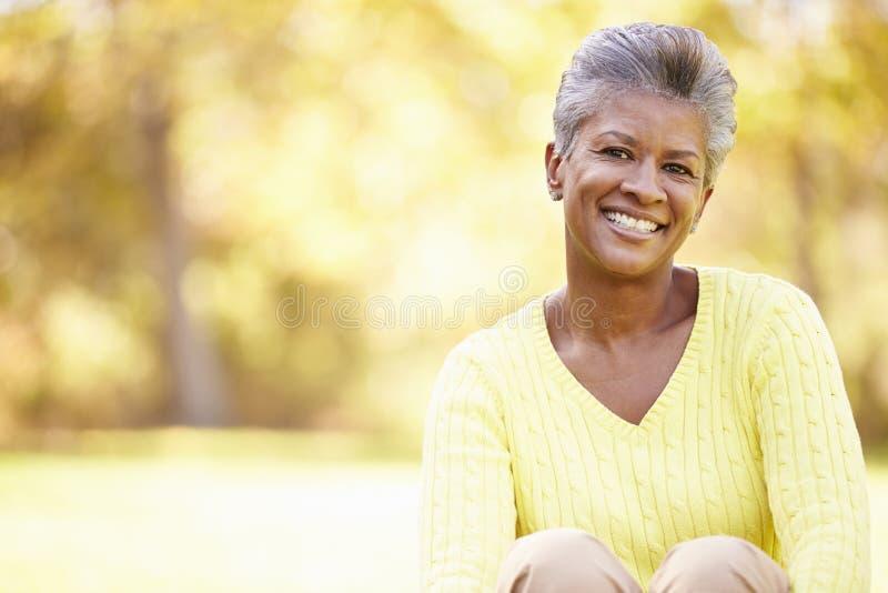 放松在秋天风景的成熟妇女 免版税库存照片