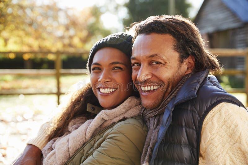 放松在秋天风景的爱恋的夫妇画象  图库摄影
