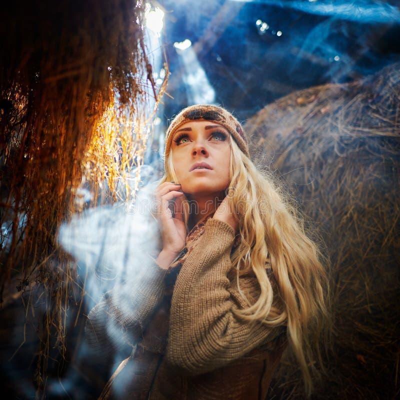 放松在秸杆的美丽的妇女在发烟性,多灰尘的室 图库摄影